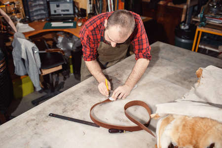 Working process in the leather workshop. Tanner in old tannery.