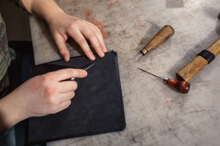 Close up of hands tanner performs work on table with tools 스톡 콘텐츠
