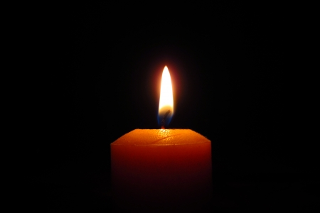 candlelight memorial: Candle close up, black background                                Stock Photo