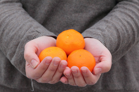 Hands holding fresh fruit, grey background photo