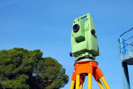 Total station, surveying instrument against blue sky