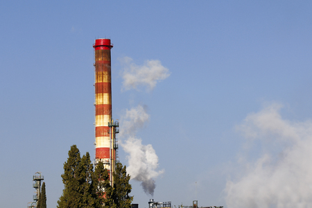 High chimney and tree in a refinery photo