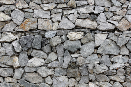 Rock wall with steel wire, gabion photo