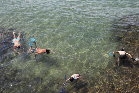 Family snorkeling in transparent water photo