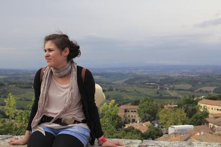 Young woman thinking, seated Фото со стока