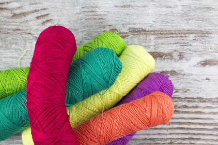 Colorful sewing threads in a wood background photo
