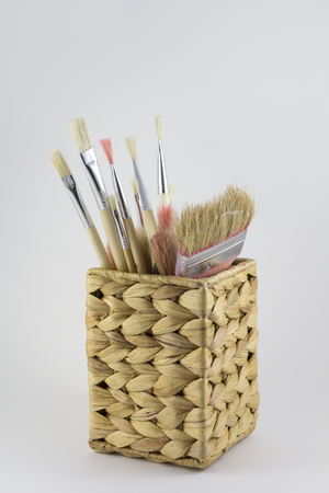 handimade: Set of paintbrushes in a wicker pot