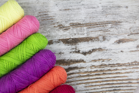 Colorful sewing threads in a wood background