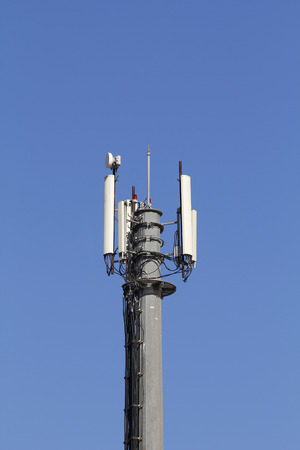 Mobile antenna in a tower against blue sky