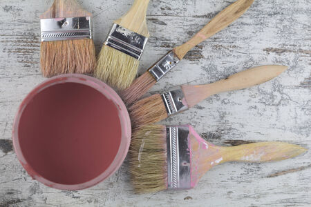 Paintbrushes and paint can in a wood background, vintage Stock Photo