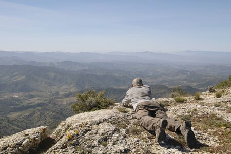 skinhead: Lying man looking to the landscape, with foggy mountains Stock Photo