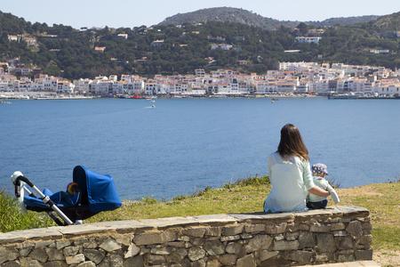 Mom and son sitting in the coast of Port de la Selva, in Catalonia, Spain