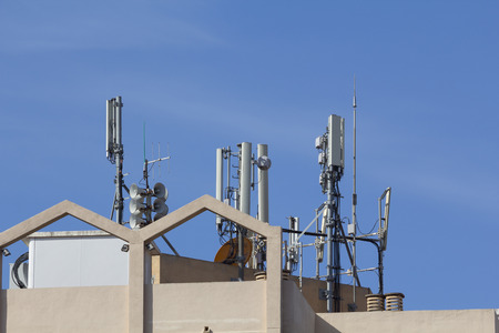 Mobile antennas in a building, against blue sky