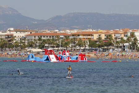 brincolin: CAMBRILS, ESPAÑA - 12 de julio 2015: Gente que se divierte en la playa en un día caluroso y soleado el 12 de julio de 2015 a la playa de Cambrils, en Cataluña, España, un destino famoso verano