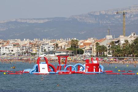 brincolin: CAMBRILS, ESPA�A - 12 de julio 2015: Gente que se divierte en la playa en un d�a caluroso y soleado el 12 de julio de 2015 a la playa de Cambrils, en Catalu�a, Espa�a, un destino famoso verano