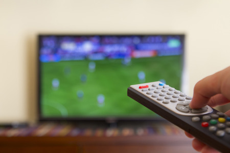 Watching a soccer match in the television, with a tv remote control in the hand Archivio Fotografico