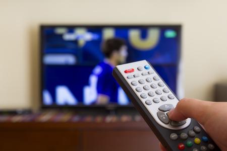 Télévision télécommande dans les mains de l'homme, en regardant un match de football Banque d'images