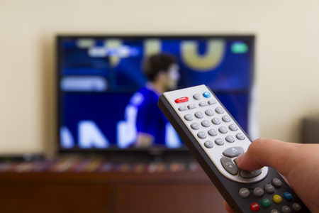 Télévision télécommande dans les mains de l'homme, en regardant un match de football Banque d'images - 43669761