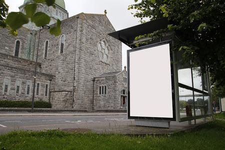 IGLESIA: Cartelera en blanco en una parada de autob�s, con una iglesia