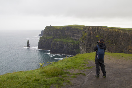 moher: Unidentified man taking a photo of Cliffs of Moher in Clare co., Ireland