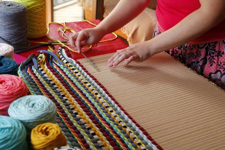 Woman hands weaving a handmade carpet Imagens