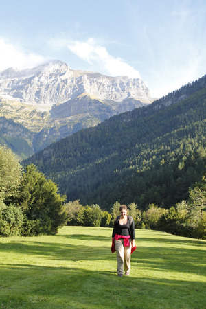 ordesa: Woman with a backpack, hiking in a green landscape, at the Pyrenees of Spain Stock Photo