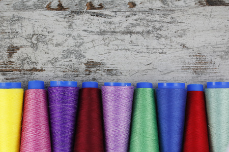 maquinas de coser: Bobinas de coser coloridos en un fondo de madera