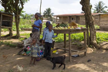 Akure, NIGERIA - 12 août 2012: Les membres d'une famille nigerian de Akure, levez-vous pour un portrait en face de leur nourriture en vente, dans un village local à l'état d'Ondo au Nigeria, le 12 Août, 2012 Banque d'images - 55337469