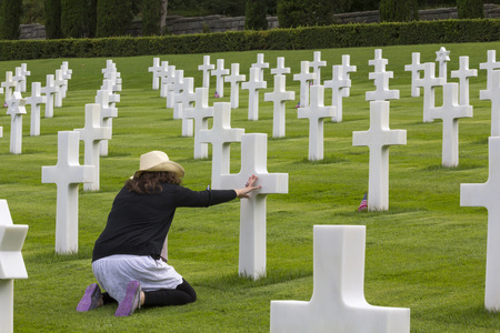 Woman praying in a memorial cemetery, for war soldiers Standard-Bild