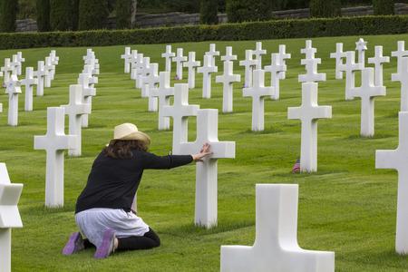 Mujer que ruega en un cementerio Memorial, de soldados de la guerra