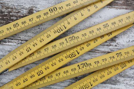 metro de medir: Madera de medición del medidor, en un fondo de madera