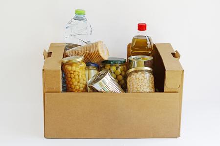 pobreza: La comida en una caja de donación, aislado en un fondo blanco