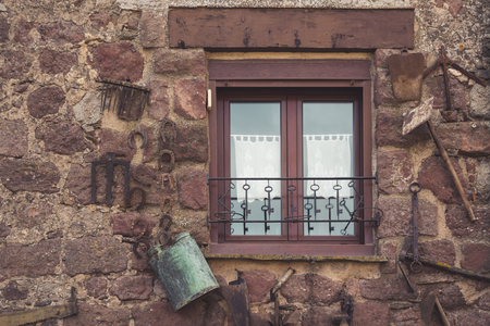 agricultural tools: Window in a stone house, Decorated with agricultural tools
