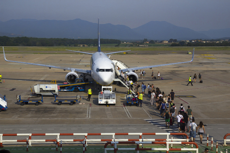 embark: BARCELONA, SPAIN - July 28, 2014: Tourists ready to embark in a low cost airplane at the terminal of the airport of Barcelona, Spain, on July 28, 2014