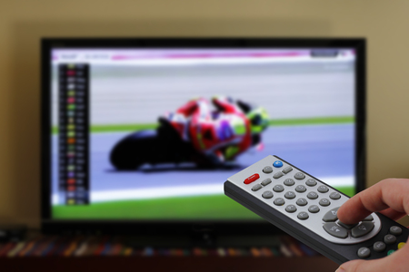 qualify: Motorbikes race in television, zapping with remote control Stock Photo