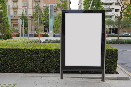 Blank billboard in the street, green plants
