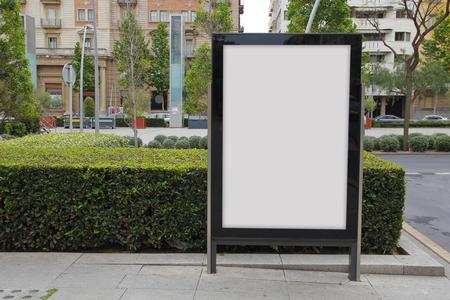 Blank billboard in the street, green plants