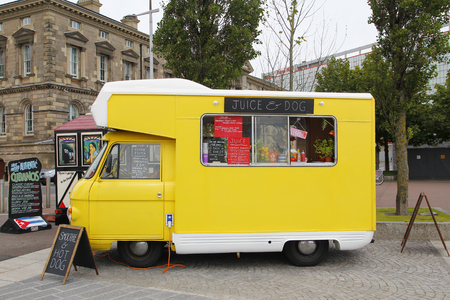 COSTUMERS: BELFAST, IRELAND - AUGUST 08, 2015: Yellow food truck of natural fruit juice and veggie food parked in the street, waiting for costumers at  the city of Belfast in Northern Ireland, on August 08, 2015 Editorial