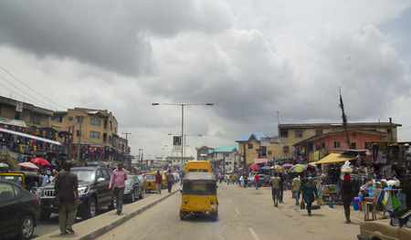 LAGOS, NIGERIA - MAY 11, 2012: People in the street in the city view of Lagos, the largest city in Nigeria and the African continent. Lagos is one of the fastest growing cities in the world