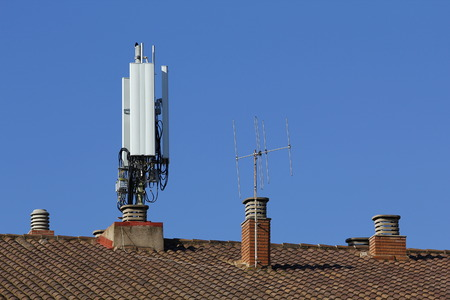 Mobile antenna in the roof of a building, against blue sky Stock Photo