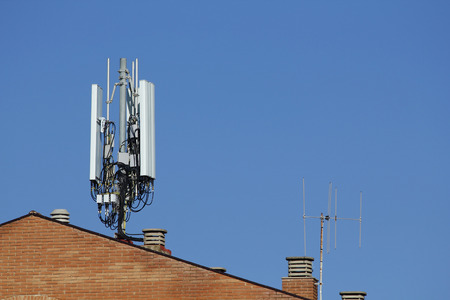 Mobile antenna in the roof of a building, against blue sky Banco de Imagens