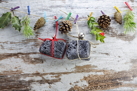 Coal Christmas gifts, hanging in a string with clothespins. Stock Photo