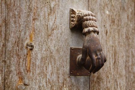 Old metal knocker in a wooden door