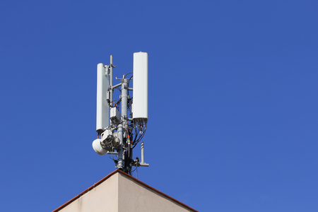 Mobile antenna in the roof of a building, against blue sky Archivio Fotografico