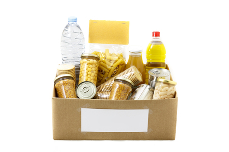 Food in a donation cardboard box, isolated in a white background Imagens