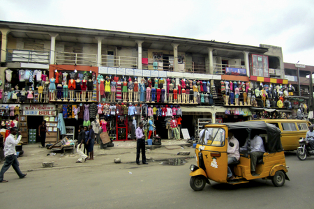 LAGOS, NIGERIA - SEPTEMBER 4, 2012: Colorful african fashion shops, with many clothes hanging in mannequins, in the large city of Lagos, Nigeria Editoriali