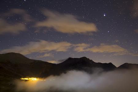 Paysage de nuit avec des étoiles et le village illuminé dans les montagnes Banque d'images