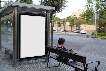 Panneau d'affichage en blanc dans un arrêt de bus, avec une jeune femme assise dans un banc Banque d'images