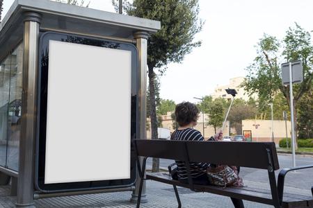 Le billboard en blanc se moque et une jeune femme prend l'autorétie
