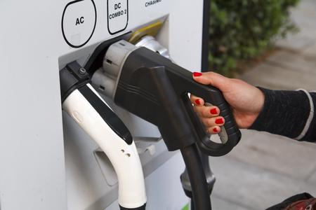 Femme mains tenant une prise électrique pour la recharge de la batterie de voiture Banque d'images